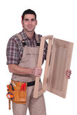 Carpenter with a cupboard door — Stock Photo