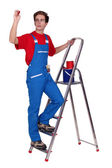 Painter on a stepladder and holding a stamp — Stock Photo