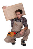 Portrait of young cabinetmaker carrying cupboard door over shoulder — Stock Photo