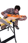 Carpenter leveling plank — Stock Photo