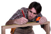 Man measuring wooden frame — Stock Photo