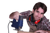 Carpenter sawing plank of wood — Stock Photo