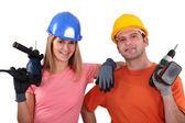 Craftsman and craftswoman holding drills — Stock Photo