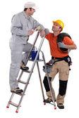 Pittore artigiano su una scala, parlando con un collega — Foto Stock