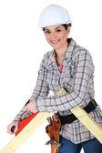 Female carpenter using a planer. — Stock Photo