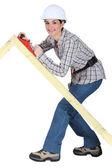 Tradeswoman using a plane to smooth a wooden frame — Stock Photo