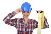 Female apprentice looking pleased with ruler and hard hat — Stock Photo
