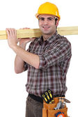 Carpenter transporting wood — Stock Photo