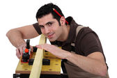 Carpenter eyeing a piece of wood — Stock Photo
