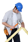 Portrait of joiner hammering down nail — Stock Photo