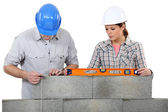 Bricklayers with a spirit level and plumb line — Stock Photo