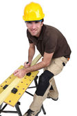 Tradesman using a plane to smooth a plank of wood — Stock Photo