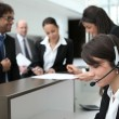 Businesspeople crowding around the reception area of their company — Stock Photo