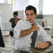 Man sat in office adjusting his tie — Stock Photo