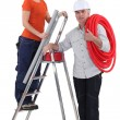 Female plumber on ladder with male tutor — Stock Photo #10349249