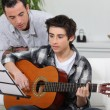 Stock Photo: Adolescent boy learning to play guitar