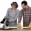 Apprentice with circular saw — Stock Photo