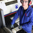 Young factory worker operating cutting machine - Stock Photo