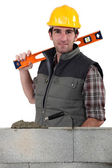 Stonemason standing before a wall and carrying a spirit level — Stock Photo
