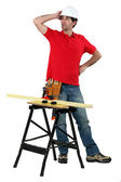 Carpenter with workbench looking puzzled — Stock Photo