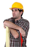 Construction worker with timber and a plane — Stock Photo