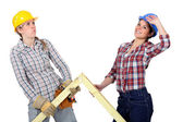 Women lifting wooden triangle — Stock Photo