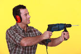 Man protecting his ears whilst drilling — Stock Photo