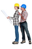 Full-body picture of young female architect and male builder against white background — Stock Photo