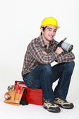 Tradesman holding a blowtorch and sitting on his toolbox — Stock Photo