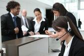 бизнесмены толпиться вокруг стойки их компании — Стоковое фото