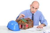 Architetto seduto con casa modello — Foto Stock