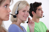 Three call-center workers sat in a row — Stock Photo