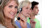 Woman and colleagues wearing headsets — Stock Photo