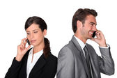 Businessman and woman with cellphones — Stock Photo