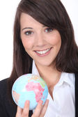 Smiling young businesswoman holding a globe — Stock Photo