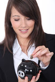 Young woman putting money into a piggy bank — Stock Photo