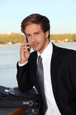 Executive on the phone at a riverside — Stock Photo