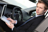Man with computer in car — Stock Photo