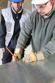 Engineer cutting sheet metal with apprentice — Stock Photo