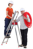 Female plumber on ladder with male tutor — Stok fotoğraf