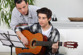 Adolescent boy learning to play the guitar — Stock Photo