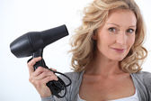 Woman with a hairdryer — Stock Photo