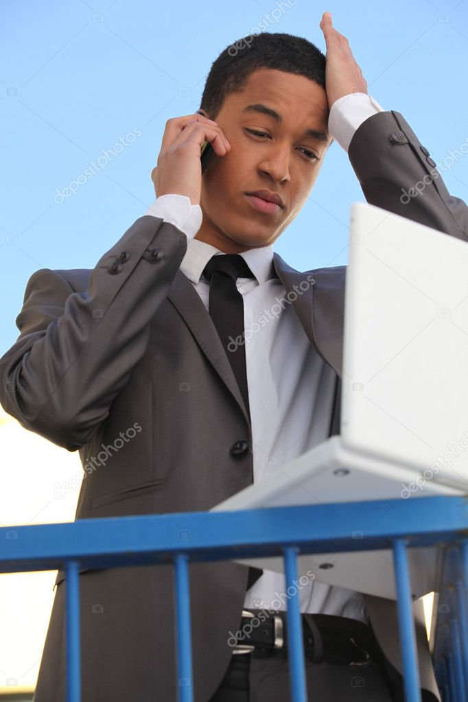 Stressed young businessman with laptop — Stock Photo #10348618