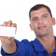 Man in blue overalls holding up a blank business card — Stock Photo #10376916