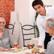 Waiter serving senior couple — Stockfoto #10377277