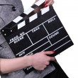Stock Photo: Woman holding clapboard on white background