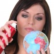 Woman spraying miniature globe - Stock Photo