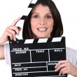 Stock Photo: Brunette womwith movie slate