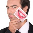 Man in a suit holding a photo of lips — Stock Photo
