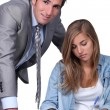 Man in suit with girl writing at desk — Stock Photo #10378126